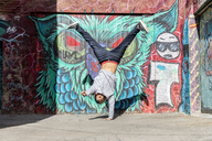 Young man with headphones doing handstand in front of graffiti - AFVF00323