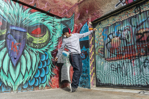 Young man liestening music with headphones dancing in front of graffiti - AFVF00329