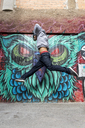 Young man jumping in the air in front of graffiti - AFVF00332
