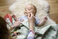 Mother touching newborn baby's face, lying on lambskin - BMOF00040