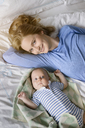 Portrait of smiling mother with her baby boy lying on bed - BMOF00067