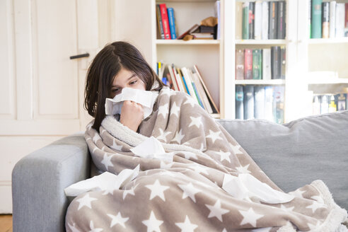 Sick girl sitting on the couch at home blowing nose - LVF06797