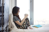 Side view of woman with coffee cup looking away while sitting on bed at home - CAVF12012
