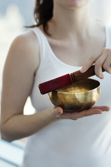 Midsection of woman meditating with singing bowl at home - CAVF12021