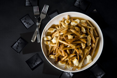 Overhead view of poutine in bowl with forks on table - CAVF12243