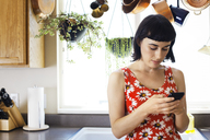 Woman using phone while leaning on kitchen counter at home - CAVF12273