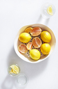 Close-up of lemons in container over white background - CAVF12336