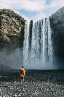 Rear view of man looking at Skogafoss waterfall - CAVF12387