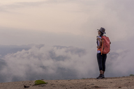 Side view of female hiker with backpack standing on mountain during foggy weather - CAVF12390