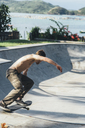 Side view of shirtless young man skateboarding at sports ramp - CAVF12411