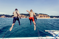 Rear view of shirtless male friends with surfboards jumping into sea against blue sky - CAVF12420