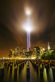 Wooden posts in river against illuminated city with Tribute in Light at night - CAVF12447