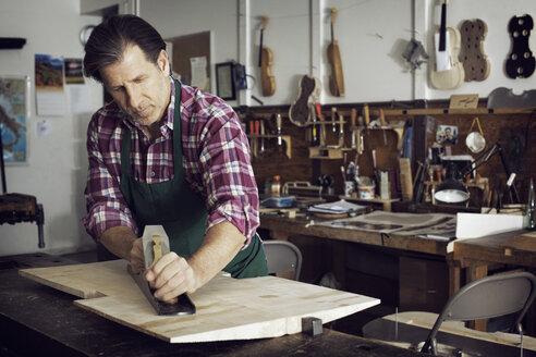 Man sawing wood while making violin in workshop - CAVF12504