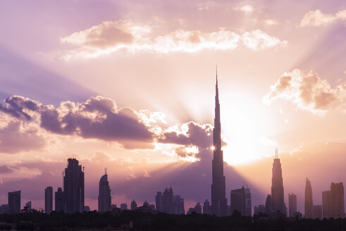 Silhouette Burj Khalifa and skyscrapers against cloudy sky during sunset - CAVF12558