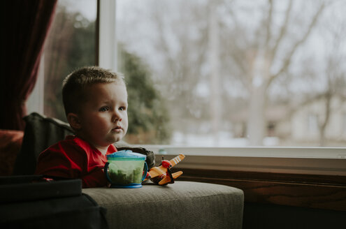 Thoughtful boy looking away while sitting on chair by window at home - CAVF12606