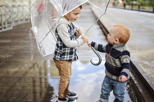 Baby boy with brother holding umbrella while standing on wet street - CAVF12615
