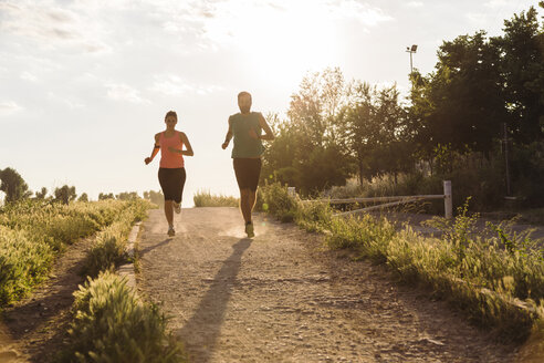 Full length of young couple jogging on dirt road at park against clear sky during sunset - CAVF12627