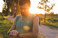 Sportsman examining wristwatch while standing at park during sunset - CAVF12633