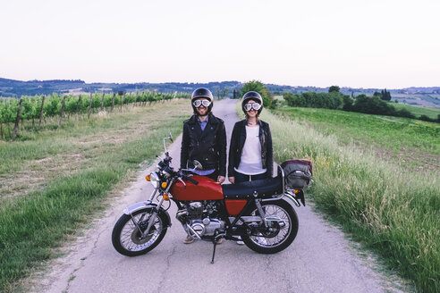 Portrait of young couple in crash helmets and flying goggles standing behind motorcycle at country road against clear sky - CAVF12654