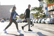 Man holding skateboard walking with girlfriend on city street - CAVF12678