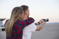 Couple taking selfie while standing at beach against clear sky - CAVF12693