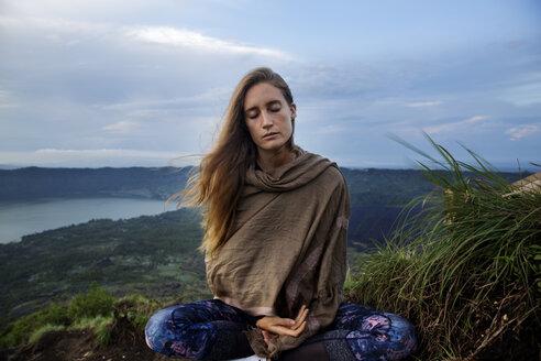 Woman meditating on mountain against sky - CAVF12726