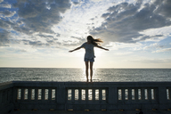 Woman with arms outstretched standing on railing by sea against sky - CAVF12741