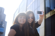 Low angle view of happy woman taking selfie with friend in city - CAVF12801