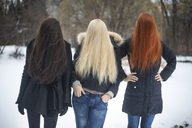 Female friends covering face with hair on field - CAVF12849