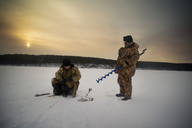Senior man and woman ice fishing on frozen lake at sunset - CAVF12858