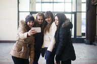 Female friends taking selfie through smart phone while standing outside building - CAVF12864