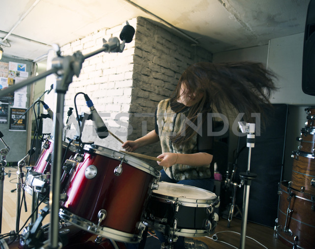 Happy woman enjoying while playing drum kit at home - CAVF12870 - Cavan Images/Westend61