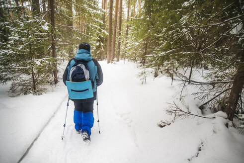 Rear view of hiker carrying backpack while walking in snow covered forest - CAVF12891