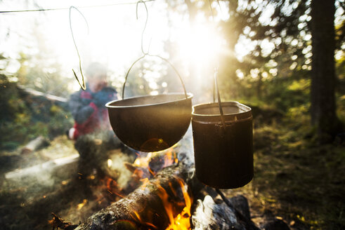 Food being cooked in utensils over bonfire on sunny day - CAVF12981