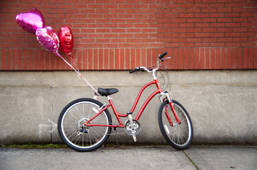 Heart shaped balloons tied to bicycle parked against wall - CAVF13068