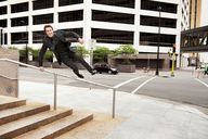 Businessman jumping over railing at sidewalk in city - CAVF13125