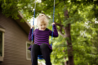 Girl enjoying on swing against trees at park - CAVF13131