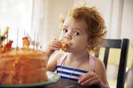 Portrait of girl eating cake while sitting at table - CAVF13149