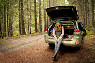 Portrait of happy woman sitting in car trunk at forest - CAVF13176