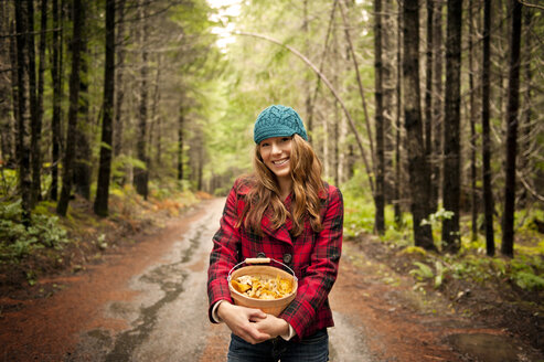 Portrait of happy woman holding mushrooms in bucket while standing on footpath in forest - CAVF13179
