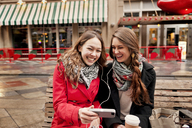 Happy female friends using phone while sitting on bench in city - CAVF13182