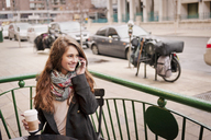 Happy woman talking on phone while sitting at sidewalk cafe - CAVF13185