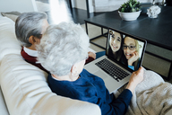 Senior couple video conferencing with granddaughters through laptop computer while sitting on sofa at home - CAVF13227