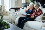 Happy senior couple video conferencing through laptop computer in living room - CAVF13233