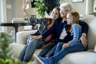 Happy grandmother and granddaughters taking selfie through smart phone while sitting on sofa - CAVF13263