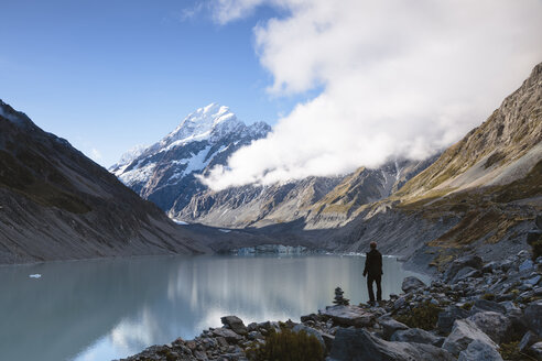 Rear view of hiker standing at lakeshore against cloudy sky at Mt Cook National Park - CAVF13311