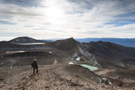 Man hiking at Mt Ngauruhoe against cloudy sky during sunny day - CAVF13320