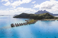 Aerial view of stilt houses by mountains at Bora Bora island - CAVF13338
