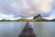 Man sitting on jetty over lagoon against cloudy sky - CAVF13341