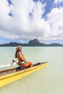 Woman in traditional clothing canoeing on lagoon of Bora Bora island against cloudy sky - CAVF13347